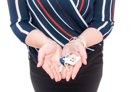 Photo pour Image recadrée de femelle agent immobilier montrant les clés de maison isolé sur fond blanc - image libre de droit