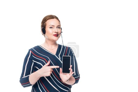 female operator of call center with headset pointing at smartphone with blank screen isolated on white background