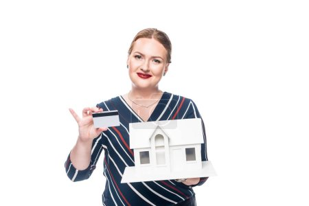 happy female estate agent showing maquette of new house and credit card isolated on white background