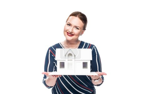 smiling female estate agent presenting maquette of house isolated on white background