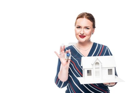 smiling female estate agent holding maquette of house with key isolated on white background