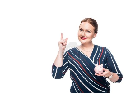 smiling businesswoman with pink piggy bank doing idea gesture isolated on white background