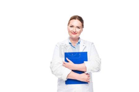 Photo pour Heureuse femme médecin en blouse blanche tenant presse-papiers isolé sur fond blanc - image libre de droit