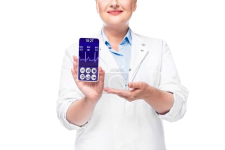 cropped image of female doctor pointing at smartphone with heart rate monitor on screen isolated on white background