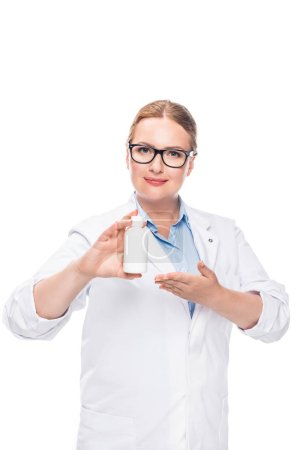 attractive female doctor in eyeglasses pointing at pill bottle isolated on white background