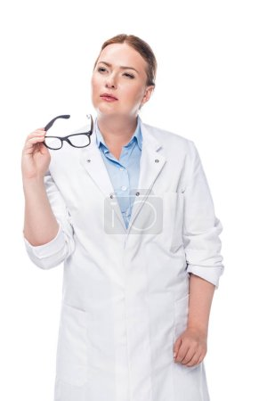 thoughtful female doctor holding eyeglasses isolated on white background
