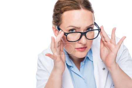serious female doctor adjusting eyeglasses and looking at camera isolated on white background