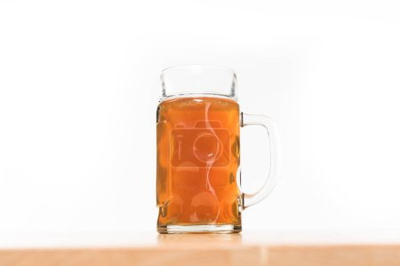 close up view of beer in mug on wooden table on white background