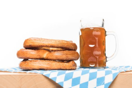 selective focus of mug of beer and pretzels on table with table cloth on white background