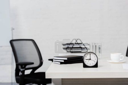 close-up shot of table with stack of notebooks and alarm clock at modern office