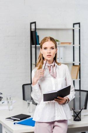 Photo pour Séduisante jeune femme d'affaires avec ordinateur portable se penchant au milieu de travail au bureau moderne - image libre de droit