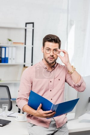 handsome young businessman with folder and eyeglasses leaning back at workplace and looking at camera