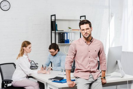 Photo for Handsome young businessman looking at camera and leaning back on table at modern office while colleagues working together on background - Royalty Free Image