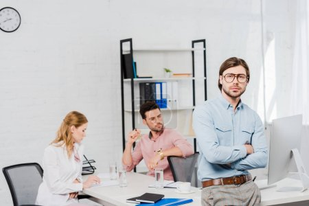 handsome young businessman with crossed arms looking at camera and leaning back on table at modern office while colleagues working together on background