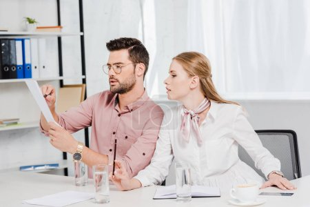 confident business colleagues doing paperwork together at modern office