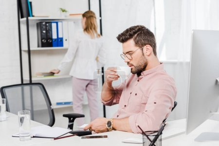 handsome young businessman drinking coffee while his secretary taking folder from shelf blurred on background