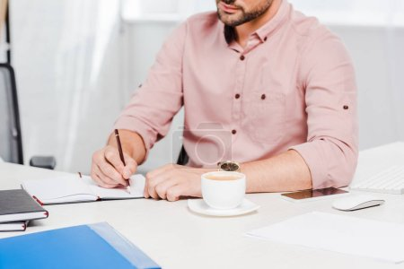 cropped shot of young businessman with cup of coffee making notes at workplace