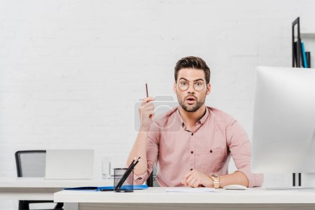 emotional young businessman with creative idea looking at camera at modern office