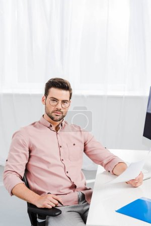 handsome young businessman looking at camera while sitting at workplace with documents