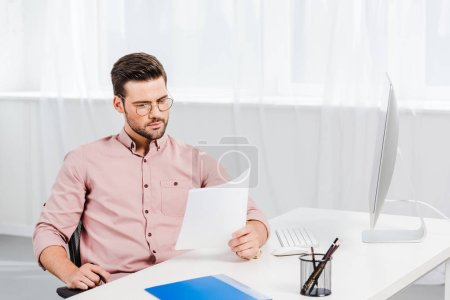 concentrated young businessman reading documents at workplace
