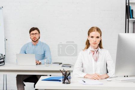 Photo pour Collègues de travail sérieux assis au milieux de travail au bureau moderne et regardant la caméra - image libre de droit