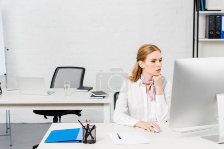 concentrated young businesswoman working with computer at modern office