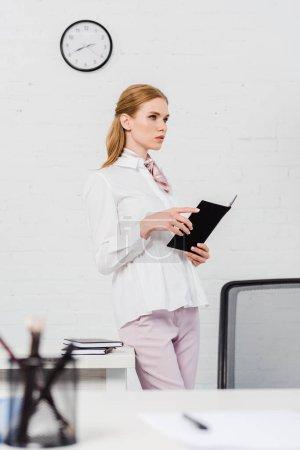 Photo pour Confiant jeune femme d'affaires avec ordinateur portable debout au bureau moderne et à la recherche de suite - image libre de droit