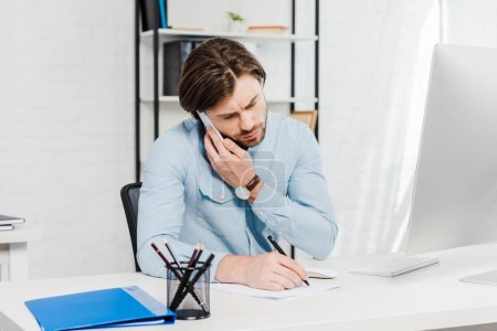 Photo for Confident young businessman talking by phone and making notes at workplace - Royalty Free Image