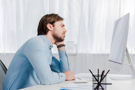 side view of depressed young businessman looking at computer monitor at office