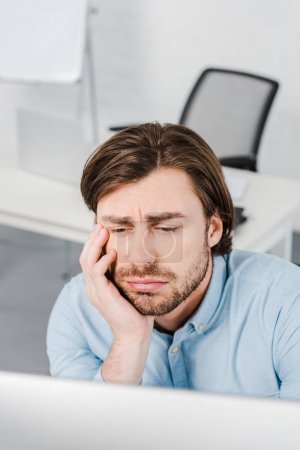 close-up portrait of depressed young businessman sitting at modern office