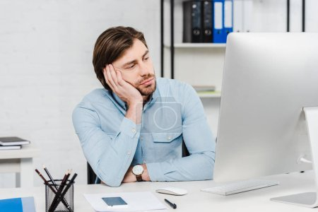 bored young businessman looking at computer monitor at modern office