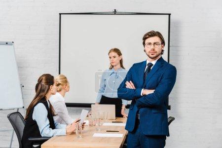 Foto de Hombre de negocios joven guapo con brazos cruzados, mirando a cámara en la oficina moderna con colegas sentados en el fondo - Imagen libre de derechos