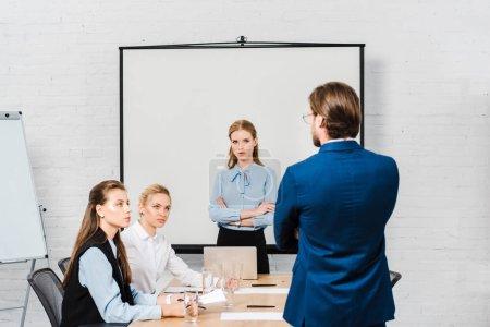 Photo pour Vue arrière du patron parlant aux gestionnaires lors d'une réunion au bureau moderne - image libre de droit