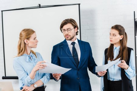 young businesswomen showing papers to their boss at modern office