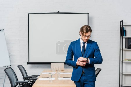 Photo for Handsome young businessman looking at wristwatch at conference hall with blank presentation board - Royalty Free Image