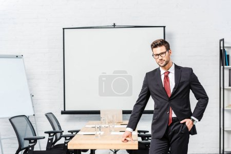 handsome young businessman looking at camera in conference hall with blank presentation board
