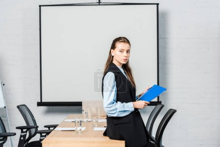 Photo for Beautiful young businesswoman with folder looking at camera in conference hall with blank presentation board - Royalty Free Image