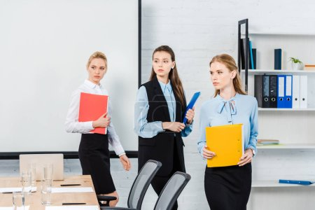 successful young businesswomen with folders of documents at modern office