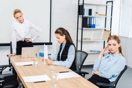 angry lady boss talking to depressed female employees at modern office