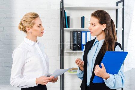Photo pour Belles jeunes femmes chefs d'entreprise ainsi que les documents de travail au bureau moderne - image libre de droit