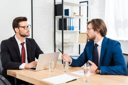successful young businessmen having conversation at modern office