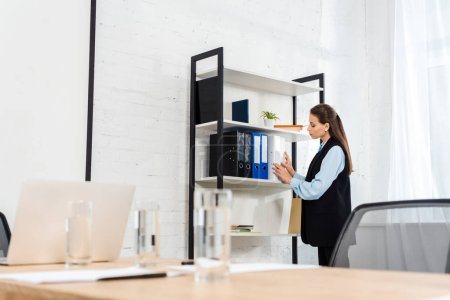 young businesswoman taking folder with documents from shelf at office