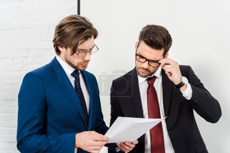 handsome successful businessmen working with documents together