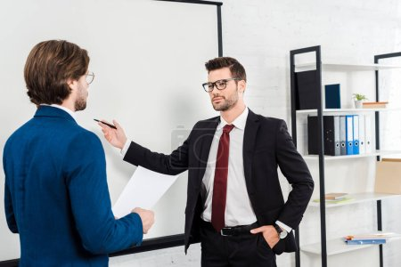 successful businessmen having conversation and pointing at presentation board at modern office