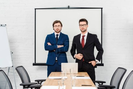 confident successful businessmen looking at camera at modern office