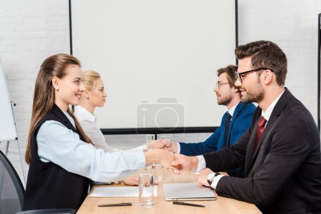 two teams of business people shaking hands during meeting at modern office
