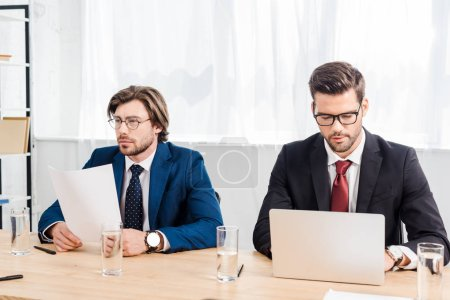 successful businessmen working with documents and laptop together at modern office
