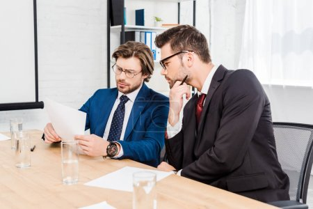 handsome successful businessmen working with documents together at modern office