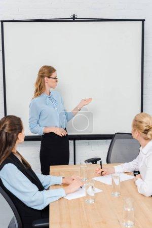 confident young businesswomen listening presentation at modern office