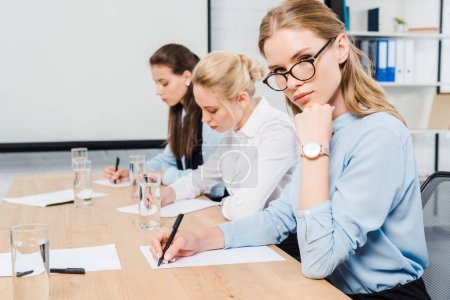 confident young businesswomen sitting at conference hall and writing documents